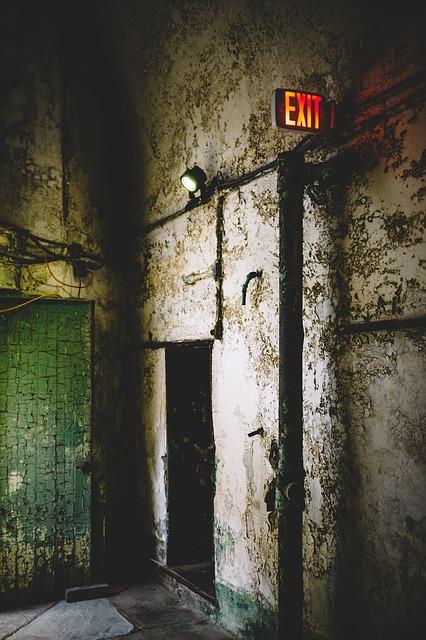 ošoupaná místnost, nápis exit červený, otevřené dveře.jpg